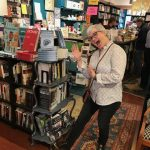 "Photo of Deb Brandon at a bookstore, by a display of her book, ""But My Brain had Other Ideas."""